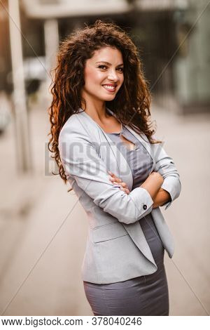 Lovely Caucasian Businessperson With Curly Hair Posing Outside