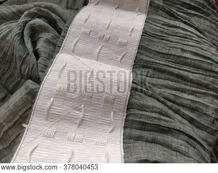 Wide White Curtain Tape Sewn To Gray Pleated Fabric. Finishing The Top Of A Curtain Or Light Tulle.