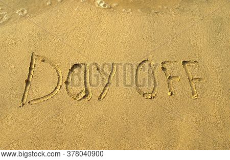 Day Off Words On Beach Sand. Day Off Phrase Is Written On A Sand With Water Waves. Top View