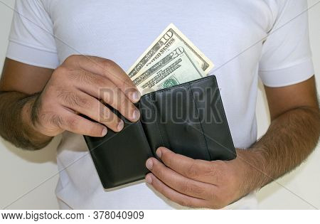 Usa National Currency. Us Dollar Money Banknotes. Man In White T Shirt Put American Dollar Banknotes