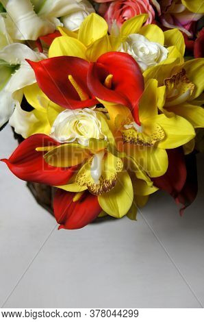 Bouquet of red and yellow flowers. Red calls. Yellow large vanilla flowers. Eternal flowers. Decorations for the holidays