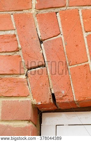 Broken Brick Arch, Cracked Mortar In Brickwork Above A Window In A Uk House. Home Maintenance And Re