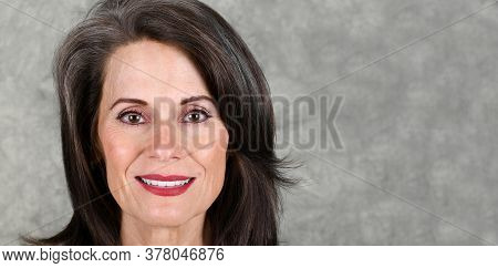 Portrait Of A Beautiful Mature Woman Against A Gray Background