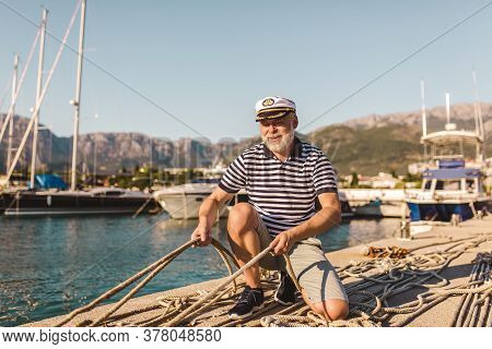Mature Man On Pier Dressed In A Sailor's Shirt And Hat Holding A Sailor Rope