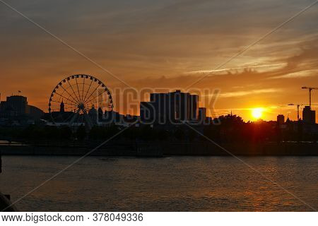 Montreal Grand Ferris Wheel In Old Port At Sunset. Reflections Of Sun Rays On Saint Laurent River.