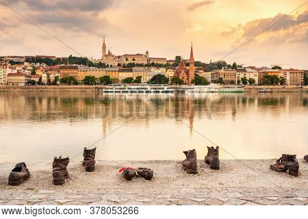 Budapest, Hungary - August 25, 2019: Shoes on the Danube Bank memorial with Buda side of Budapest  at background. Budapest cityscape with the Buda Castle, St Matthias and Fishermen's Bastion at sunset