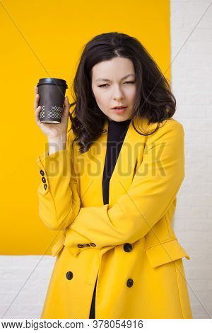 Wrong Drink, Strange Taste. Young Brunette In A Yellow Jacket Holds A Cardboard Cup Of Coffee To Tak