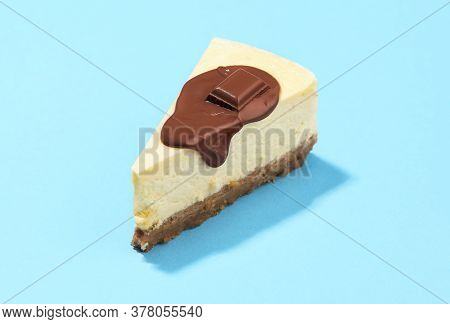 Cheesecake Slice With Melted Chocolate And Cracker Crust, On A Blue Background. Close-up Of A Slice