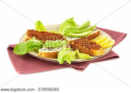 Sandwiches With Cheese, Sundried Tomatoes, Avocado And Seeds, Lettuce, Lemon On Beige  Plate On Towe