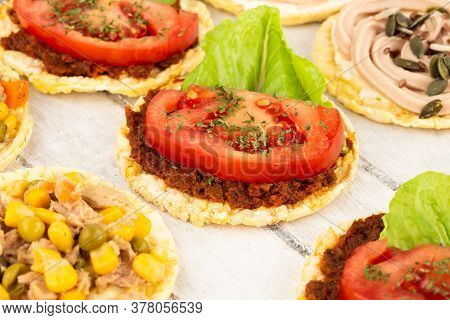 Quinoa Crackers With Olive And Sundried Tomatoes Paste, Tuna Fish And Vegetables On Gray Wooden Back