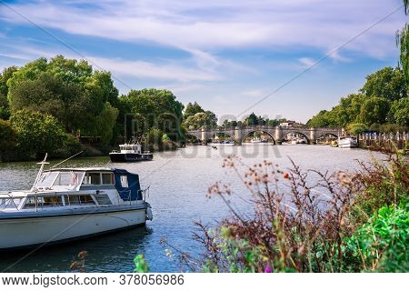 Thames Riverfront With Many Boats And Bridge In Richmond, London, Uk.