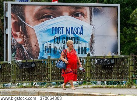 Bucharest, Romania - July 13, 2020: A Woman Walk In Front Of An Advertisement, Part Of A Campaign Pa