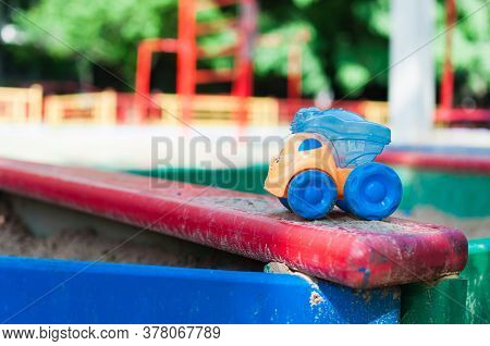 Children's Playground With Empty Sandbox And Abandoned Colorful Toy Car.