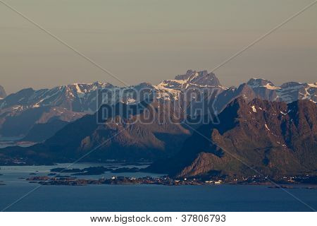 Scenic mountain peaks on Lofoten islands in Norway lit by midnight sun with small fishing village by the coast poster