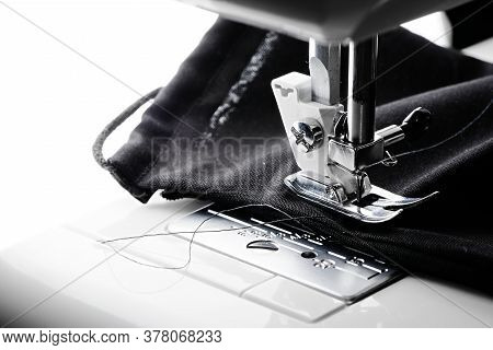 An All Black Face Covering Is Stitched In A Sewing Machine. Blank White Copy Space To The Left Hand