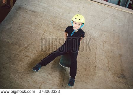 Portrait Of Boy Sit On Skateboard While Ride On Sports Ramp At Park. Urban Child With Skate Board On