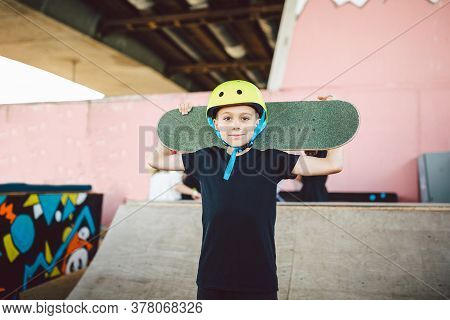 Caucasian Child Skateboarder Posing With Skate Board On Shoulders An Outdoor Skate Park. Portrait Of