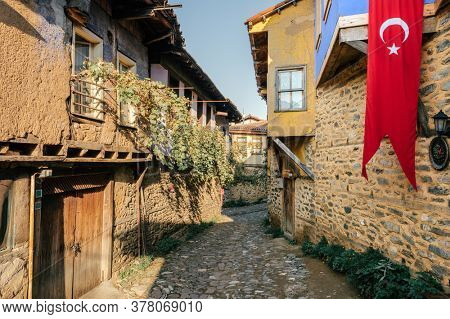 Cumalikizik village is a 700 years old Ottoman village in Turkey. Old Ottoman village in Bursa city, Turkey. Narrow street with old Ottoman houses and turkish flag