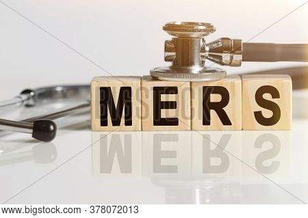 Mers The Word On Wooden Cubes, Cubes Stand On A Reflective White Surface, On Cubes - A Stethoscope.