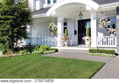 Beautiful new luxury home exterior in summer. Custom house with a porch and professional landscaping in Canada.