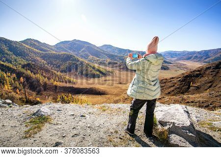 Hiker On Mountain Top With Smartphone. Woman Enjoying Landscape Of Autumn Mountains. Concept Autumn