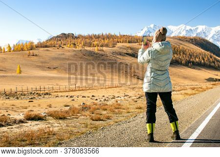 Woman Enjoying Landscape Of Autumn Mountains. Woman Hiker Taking Photo With Smart Phone.