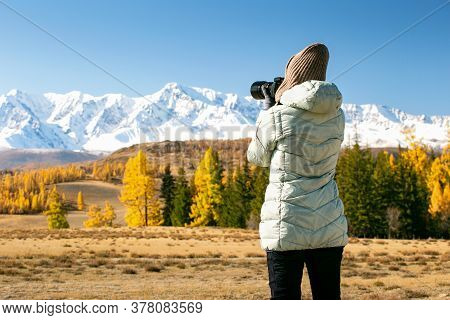 Woman On Mountain Hike In Autumn. Woman Tourist Taking Photo.
