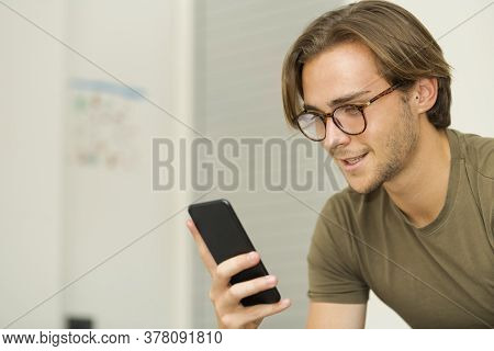 Close Up Of A Smiling Handsome Young Man Wearing Glasses Checking His Phone On An Out Of Focus Backg