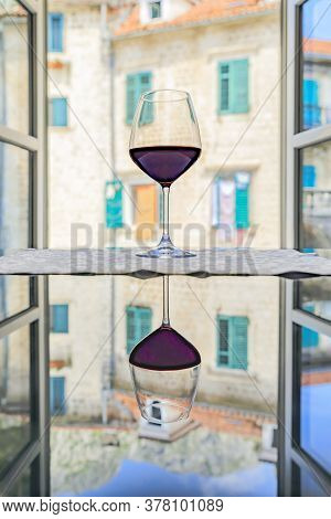 Glass Or Red Wine With Reflection And A Blurred View Of Stone Houses And Mountains Through An Open W