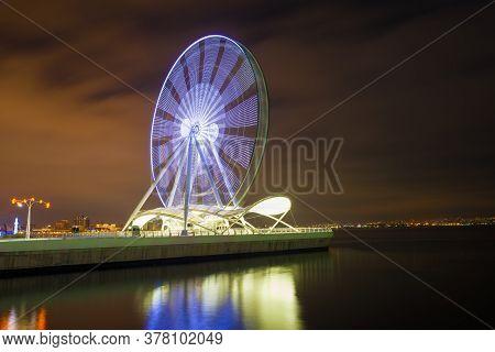 A Working Ferris Wheel On The Background Of Baku Bay On A Winter Night. Baku, Azerbaijan