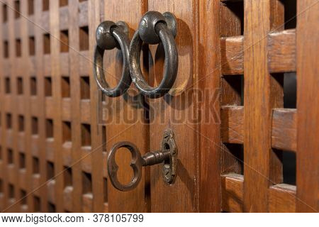 An Antique Key In An Old Wooden Cupboard