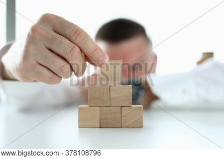 Man In Shirt Build Tower Of Wooden Cubes On Table In Office Close Up. Work In Professional Company.