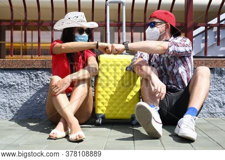 Handsome Man And Beautiful Woman Sit On Pavement On Platform Of Train Station With Yellow Suitcase I