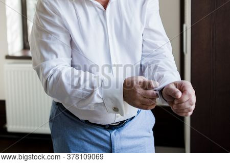 The Groom Buttons Up Cuffs Of The Shirt Sleeves