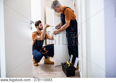 Full Length Shot Of Two Locksmith, Repairmen, Workers In Uniform Installing, Working With House Door