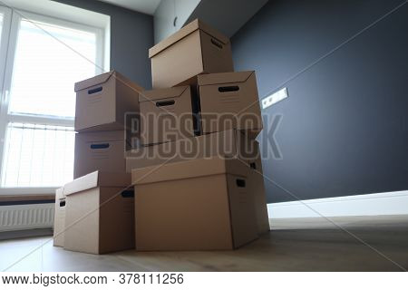 Many Cardboard Boxes Stand One Over One In Empty Room. Cargo Transportation Company. Loader Services