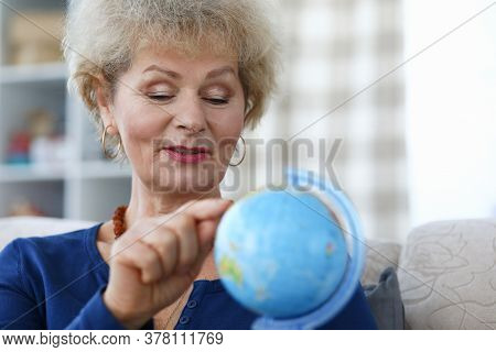 Elderly Woman Hold Blue Globe In Her Hand And Point To Continent With Her Index Finger. Traveling Ar