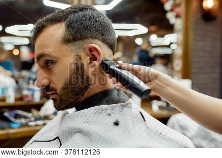 Side View Of A Young Handsome Bearded Man Getting New Trendy Haircut While Visiting Modern Barbersho