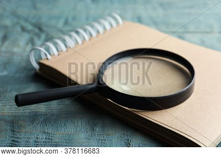Magnifier Glass And Empty Notebook On Light Blue Wooden Background, Closeup. Find Keywords Concept