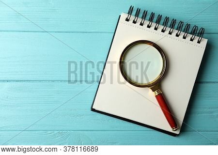 Top View Of Magnifier Glass And Empty Notebook On Light Blue Wooden Background, Space For Text. Find
