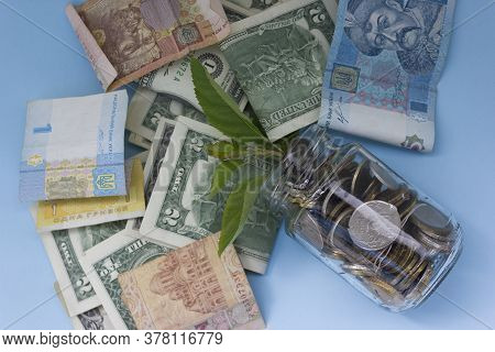 Us Dollar Banknotes And Banknotes Of Different Countries In Glass Jars There Are Many Coin And Trees