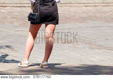 Young Woman Waiting For A Traffic Signal At A Crosswalk On Sunny Summer Day
