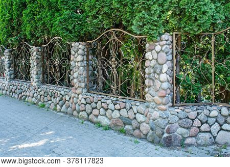 Beautiful Patterned Wrought Iron Fence With Stone Pillars On Sunny Summer Day