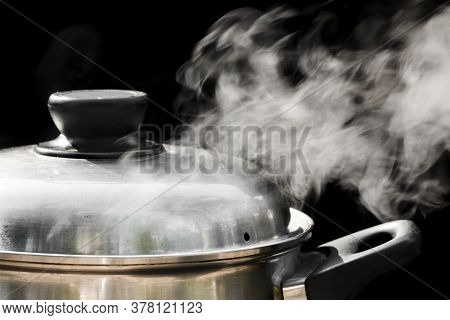 Steam Over Cooking Pot On Black Background