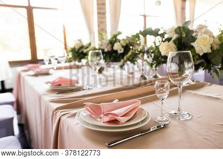 Close Up Of Festive Table Setting With Empty Wineglasses. Selebration Banquet With Pink Napkins, Whi
