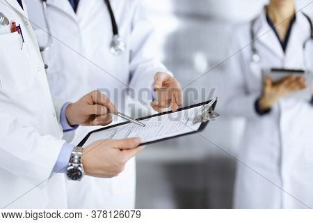 Unknown Doctors, Two Men And A Woman, Discuss Medical Exam Resoults, While Standing At Hospital Offi