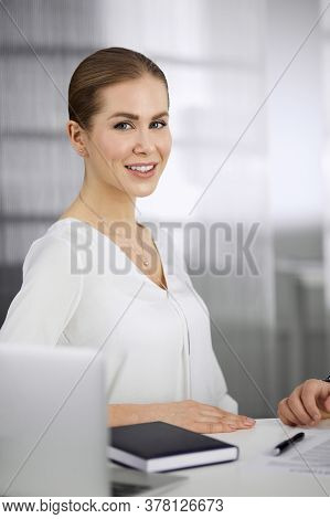 Businesswoman Sitting And Looking At Camera In Office. Business Headshot