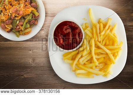 French Fries With Ketchup On Brown Wooden Background. French Fries On White Plate Wtth Vegatable Sal