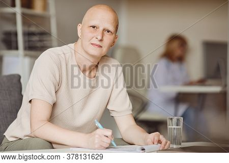 Warm Toned Portrait Of Adult Bald Woman Looking At Camera While Filling In Papers At Doctors Office