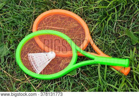Two Children's Tennis Rackets With A Shuttlecock On A Green Grass. Outdoor Activities With Children.